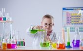 picture of naturalist  - Image of funny young chemist pouring reagent into flask - JPG