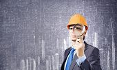 Young man engineer with magnifier against sketch background