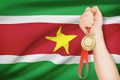 Medal In Hand With Flag On Background - Republic Of Suriname