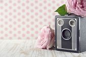 foto of hazy  - Old classic nostalgic box camera with pink roses on vintage shabby chic background - JPG