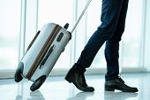 picture of pulling  - Business traveler pulling suitcase and holding passport and airline ticket - JPG