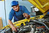 foto of gasoline station  - auto mechanic repairman tighten screw with spanner during automobile car maintenance at engine repair service station garage - JPG