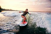 foto of watersports  - Young woman surfboarding at summer resort - JPG
