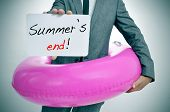 stock photo of floaties  - businessman with a pink swim ring showing a signboard with the text summers end written in it - JPG