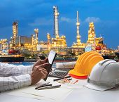 stock photo of engineering construction  - engineering working on computer tablet against beautiful oil refinery background - JPG