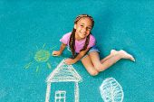 image of playground  - Nice looking black girl drawing with chalk on playground looking up with smile - JPG