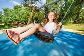 stock photo of swing  - Beautiful little girl swinging on swings on playground looking to camera in motion and smiling - JPG