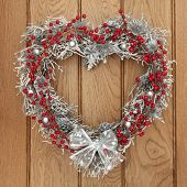 picture of yule  - Heart shaped christmas yule wreath with red and silver bauble decorations over oak background - JPG