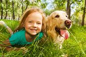 stock photo of petting  - Funny wide angle portrait of happy smiling little girl and her happy golden retriever dog pet laying in the grass of sunny summer park - JPG