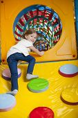 picture of climb up  - Young girl climbing up ramp into tunnel at soft play centre - JPG