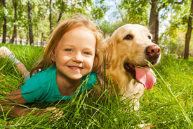 pic of labrador  - Funny wide angle portrait of happy smiling little girl and her happy golden retriever dog pet laying in the grass of sunny summer park - JPG