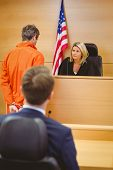 picture of court room  - Judge and criminal speaking in front of the american flag in the court room - JPG