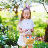 picture of bunny ears  - Adorable little girl wearing bunny ears holding a basket with Easter eggs in a blooming garden on spring day - JPG