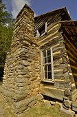 foto of log cabin  - An old log cabin setting on a rock foundation has a stone chimney reaching two stories high - JPG