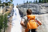 picture of waterfalls  - Hiker hiking with backpack looking at waterfall in Yosemite park in beautiful summer nature landscape - JPG