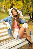 stock photo of debonair  - Happy young woman dressed in a white bear hat resting in autumn park - JPG