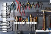 stock photo of tool  - mechanic tools hanging on a organized metal board at a vehicle reparation workshop - JPG