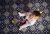 stock photo of girl toy  - Cute little baby girl playing with toys on a carpet in a living room - JPG