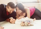 stock photo of young baby  - Happy young parents with their little baby girl at home