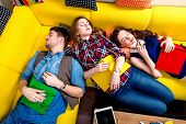 stock photo of sleeping  - Sleeping and tired young students felt sleep after work on the yellow couch - JPG