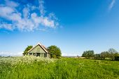 foto of neglect  - Neglected and sagging wooden barn with chipping paint in a colorful rural landscape on a clear day in the early spring season.