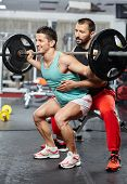 stock photo of squat  - Personal instructor helping an athlete with his barbell squats - JPG