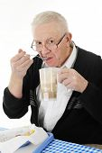 stock photo of bifocals  - A senior adult man peering over his glasses as he eats ice cream from his root beer float - JPG