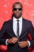 pic of shot glasses  - Serious young African man in formalwear and glasses buttoning his jacket and looking at camera while standing against red background - JPG