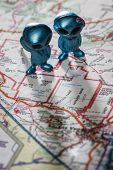 stock photo of united we stand  - toy ETs standing on a Map of the United States with the words Nevada test Site on the map - JPG