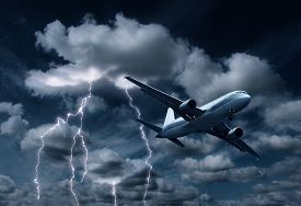 stock photo of aeroplan  - Passenger aeroplane yielding turbulent thunderstorm and lightnings - JPG