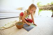 foto of schoolgirls  - Shot of innocent little caucasian girl sitting on floor coloring a picture with color chalks - JPG