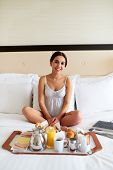 picture of bed breakfast  - Attractive woman in nightgown smiling and relaxing in bed with breakfast tray and books - JPG