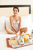stock photo of bed breakfast  - Attractive woman in a nightgown sitting cross legged in bed with breakfast tray - JPG