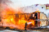 picture of firemen  - Fireman extinguishes a fire in an old wooden house - JPG