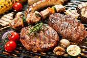 stock photo of grilled sausage  - Assorted delicious grilled meat with vegetable over the coals on a barbecue - JPG