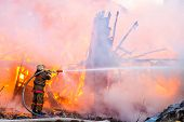 stock photo of fire  - Fireman extinguishes a fire in an old wooden house - JPG