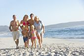 foto of extend  - Extended Family Walking Along Sandy Beach By Sea - JPG