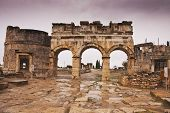 foto of ancient civilization  - The ruins of entrance gate of ancient Hierapolis at cloudy day - JPG