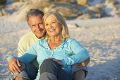 foto of couple sitting beach  - Senior Couple On Holiday Sitting On Sandy Beach - JPG