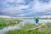 pic of stand up  - senior male with stand up paddleboard on lake shore watching stormy clouds - JPG