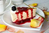 pic of cheesecake  - Tasty piece of cheesecake with berry sauce on plate on table close up - JPG