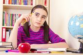 stock photo of schoolgirls  - Little schoolgirl holding a pencil and thinking - JPG