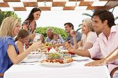 stock photo of extend  - Extended Family Group Enjoying Outdoor Meal Together - JPG