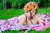 stock photo of knitted cap  - baby girl outdoors in a brown knitted cap - JPG