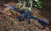 pic of rifle  - Assault rifle that is black that is in some thick trees - JPG