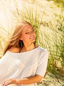 picture of dune grass  - Portrait of beautiful young woman breathing fresh air with closed eyes while sitting on beach sand dunes with grass and enjoying the sun on vacation - JPG
