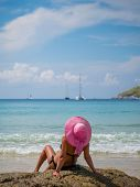 foto of beach hat  - Summer vacation woman on the beach in beach hat enjoying summer holidays looking at the ocean - JPG