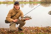 picture of fisherman  - A young man with a fish in his hands and spinning - JPG