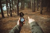 foto of pov  - Traveler woman holding a compass and pointing direction in the forest - JPG