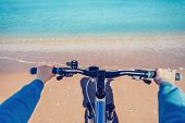 picture of pov  - Woman holding handlebar of bicycle on beach in summer - JPG